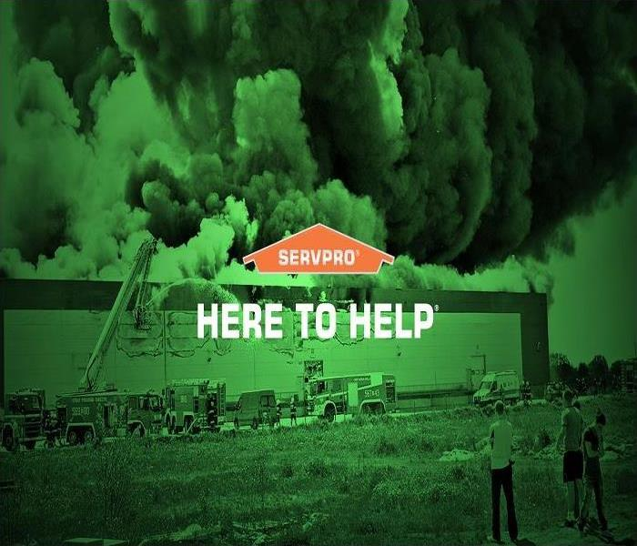 Picture showing a burning building with fire trucks and onlookers in foreground and SERVPRO logo with white text HERE TO HELP